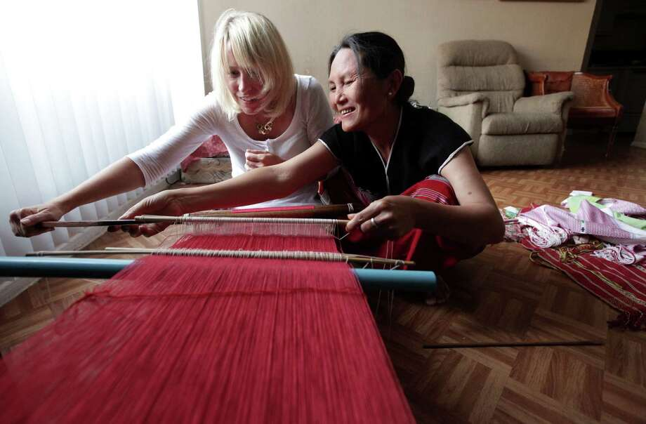 Moo Htoo, a native of Myanmar, shows Community Cloth co-founder Roxanne Paiva how to weave. Through the nonprofit group, women refugees learn business skills by selling their crafts, such as scarves, baskets and jewelry. Photo: Mayra Beltran / © 2012 Houston Chronicle