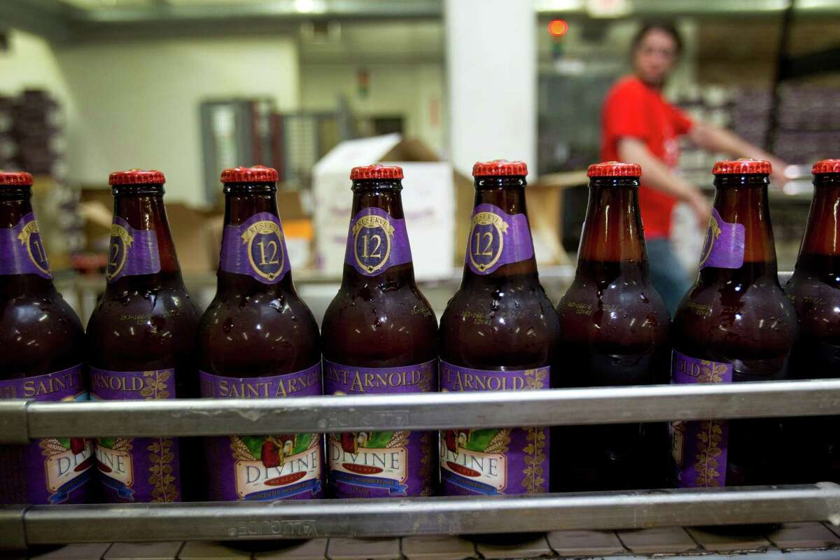 A line of Divine Reserve No. 12 bottles run along the production line after being labeled at Saint Arnold Brewing Co.