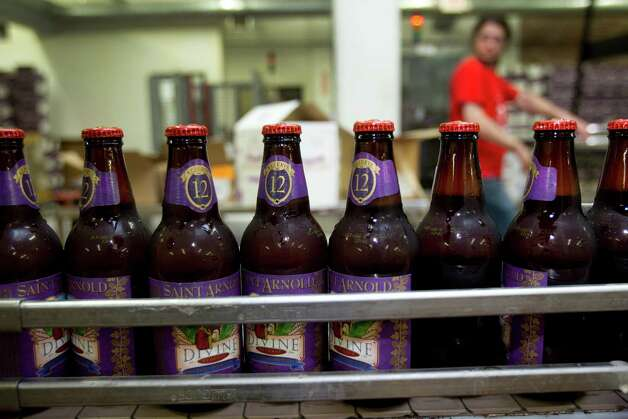 A line of Divine Reserve No. 12 bottles run along the production line after being labeled at Saint Arnold Brewing Co. Photo: Brett Coomer / Houston Chronicle