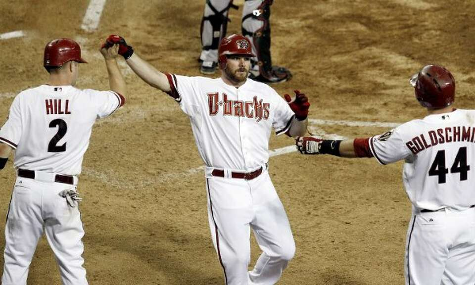 The Diamondbacks' Jason Kubel gets high-fives from teammates Aaron Hill and Paul Goldschmidt after s