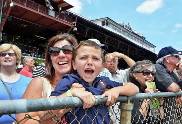 "Jennifer Polaro of Poestenkill holds her son Anthony, 5, up to the rail as he yells ""use the whip, use the whip!"" during the first race at Saratoga Race Course's opening day Friday July 20, 2012.  Jennifer says that Anthony has been coming to the races since he was a baby.(John Carl D'Annibale / Times Union) Photo: John Carl D'Annibale / 00018477B"