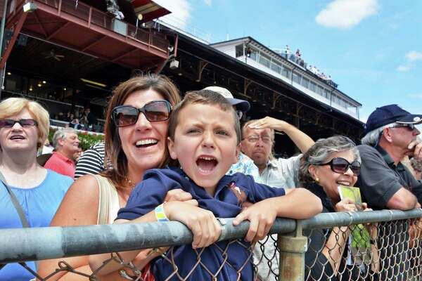 """Jennifer Polaro of Poestenkill holds her son Anthony, 5, up to the rail as he yells """"use the whip, use the whip!"""" during the first race at Saratoga Race Course's opening day Friday July 20, 2012. Jennifer says that Anthony has been coming to the races since he was a baby.(John Carl D'Annibale / Times Union)"""