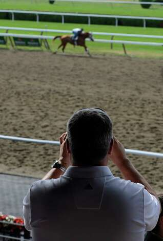A race fan watches the morning works at the Saratoga Race Course on opening day 144 July 20, 2012.  (Skip Dickstein / Times Union) Photo: SKIP DICKSTEIN