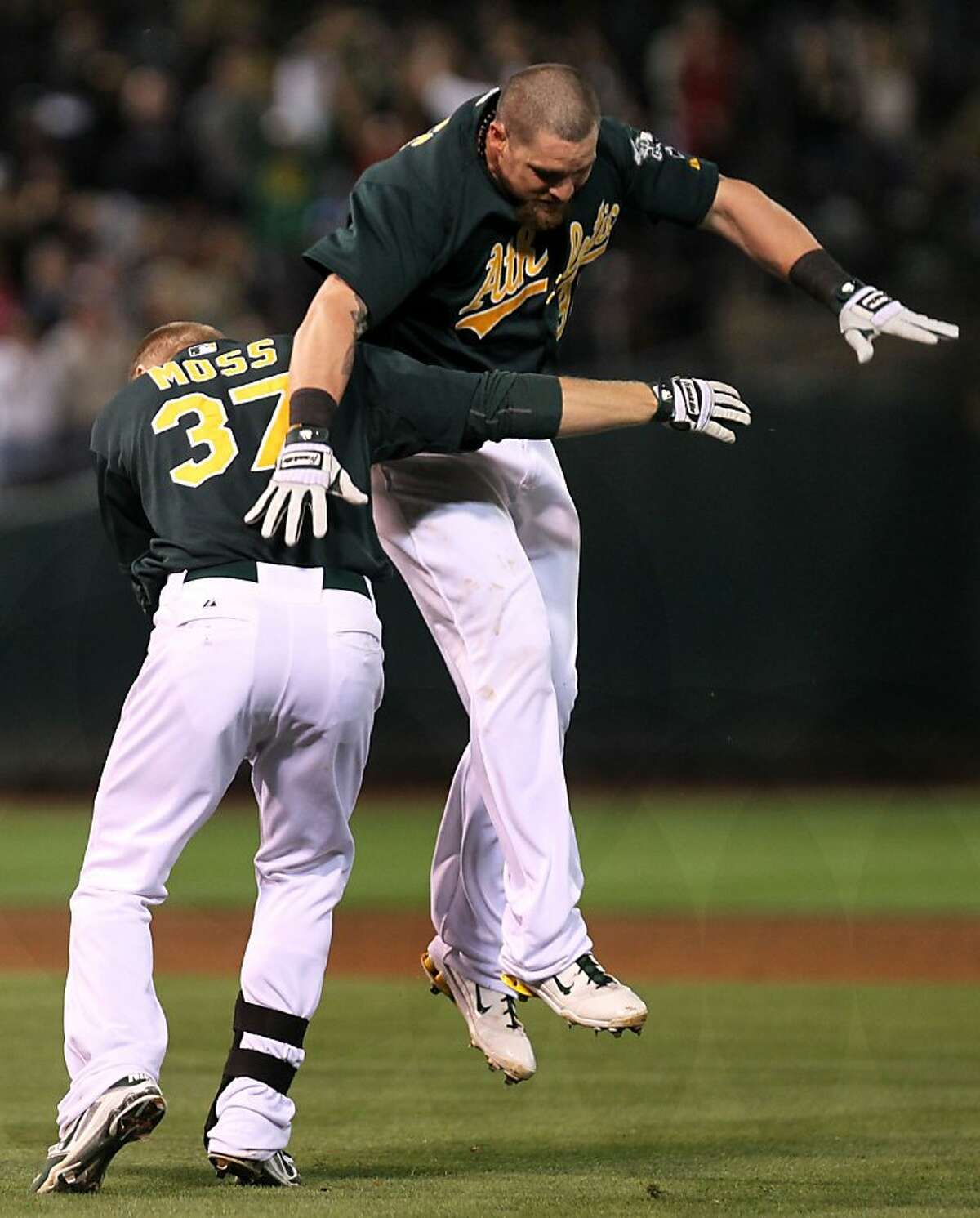 Oakland Athletics Brandon Moss celebrates his walk-off base hit that scored the A's winning run with teammate Jonny Gomes in the 9th inning of their MLB baseball game with the New York Yankees in Oakland Calif., Friday, July 20, 2012.