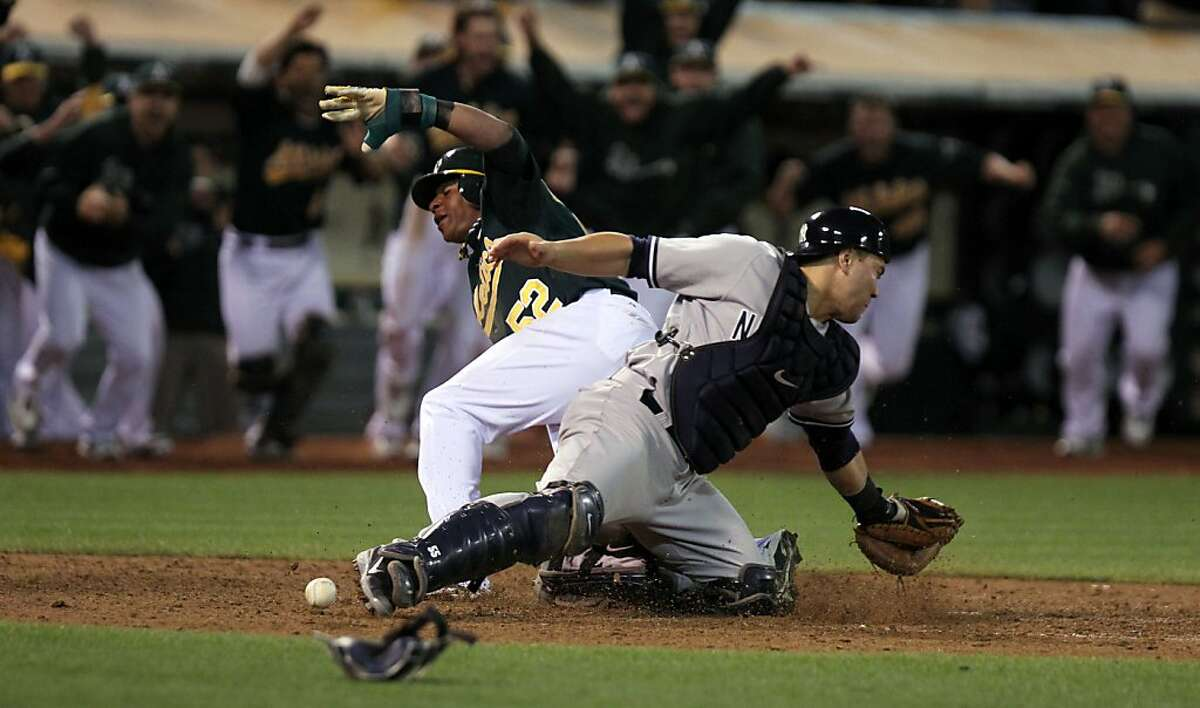 Oakland Athletics Yoenis Cespedes scores the A's winning run off a single by teammate Brandon Moss in the 9th inning of their game with the New York Yankees in Oakland Calif., Friday, July 20, 2012.