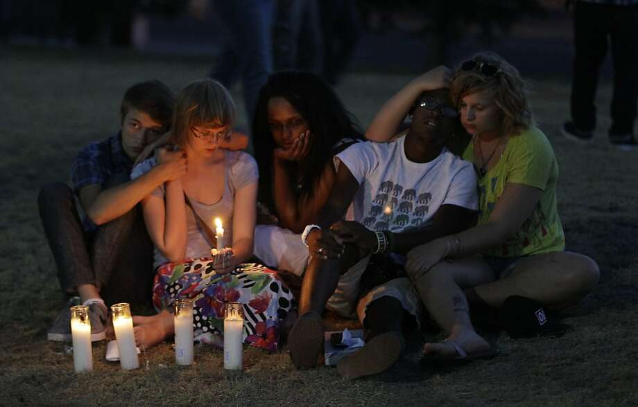 People attending a candle-light prayer gathering sit comfort each other, Friday, July 20, 2012, in Aurora, Colo., across the street from the movie theater where a gunman killed at least 12 people and wounded dozens of others Friday in one of the deadliest mass shootings in recent U.S. history. (AP Photo/Ted S. Warren) Photo: Ted S. Warren, Associated Press