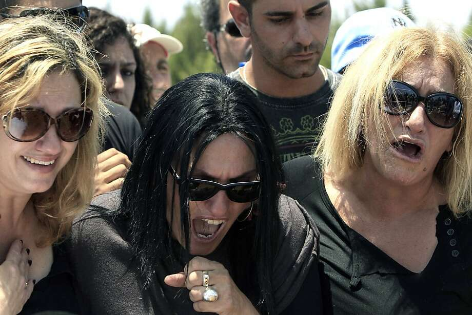 Relatives mourn during the funeral of  Kochava Shriki, 44, who was killed in a suicide bombing in Bulgaria Wednesday, in Rishon Lezion, Israel, Friday July 20, 2012. Israeli and American officials have blamed the Iran-backed Lebanese militant group Hezbollah for the bombing which killed five vacationing Israelis in a  blast in the popular Black Sea resort town of Burgas, along with a Bulgarian bus driver and the bomber. (AP Photo/Tsafrir Abayov) Photo: Tsafrir Abayov, Associated Press