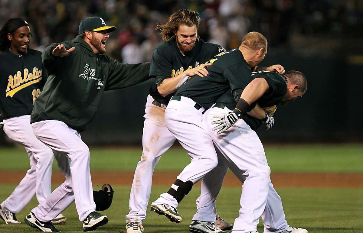 The Oakland Athletics celebrate their 3-2 win over the New York Yankees in Oakland Calif., by jumping on Brandon Moss second from right who hit a single in the 9th inning scoring Yoenis Cespedes Friday, July 20, 2012.