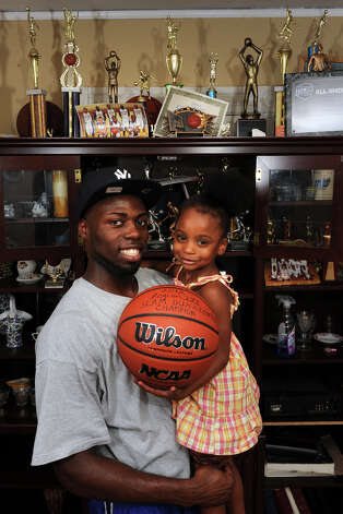 Jerome Parkins holds his daughter, Ashani, in their Bridgeport, Conn. home July 18th, 2012. Parkins played basketball in Central High School. Photo: Ned Gerard / Connecticut Post