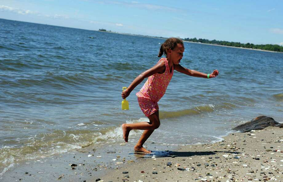 Six-year-old Isabella Spencer, of Fairfield, splashes in the Long Island Sound during the Gathering of the Vibes at Seaside Park in Bridgeport, Conn. Saturday, July 21, 2012. Photo: Autumn Driscoll / Connecticut Post freelance