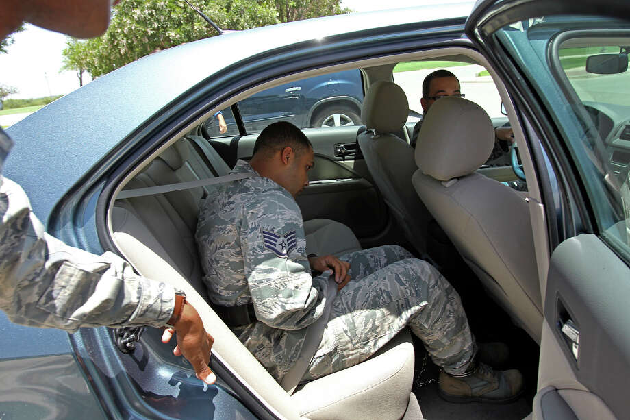 Air Force personnel try to conceal Air Force Sgt. Luis Walker as he is taken away in chains from  the 37th Training Wing Headquarters after sentencing on July 21, 2012. Photo: Tom Reel, San Antonio Express-News / ©2012 San Antono Express-News