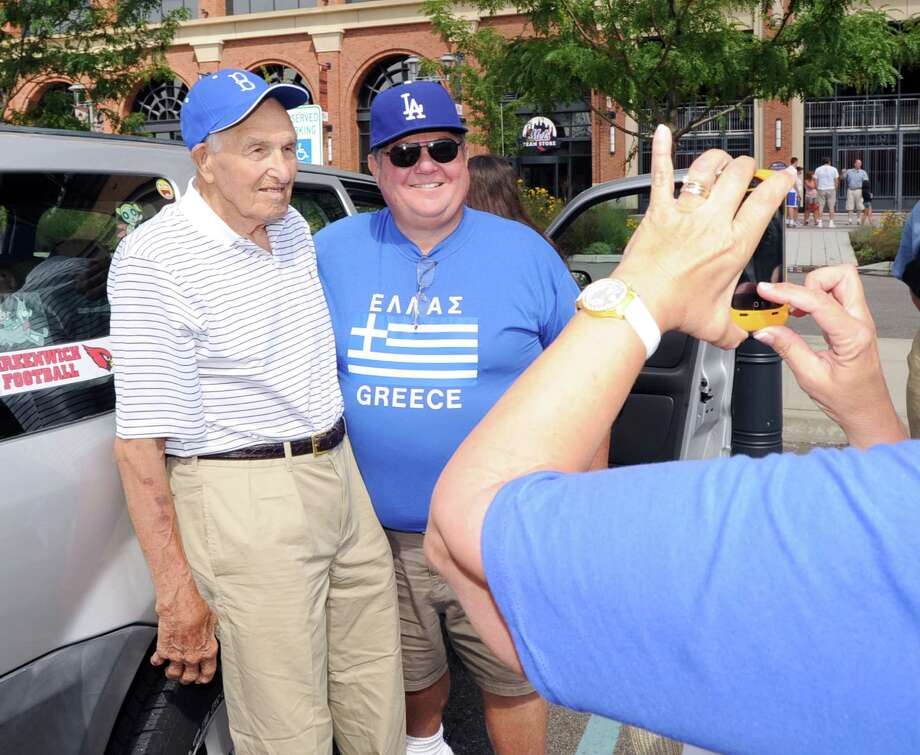 At left, Mike Sandlock, 96, a native of Old Greenwich, Conn., the oldest living former Brooklyn Dodgers player, poses for a photo with friend, Steve Riner of Morristown, Tenn., on the field during batting practice before the Los Angeles Dodgers-New York Mets baseball game on Saturday, July 21, 2012, at Citi Field in New York. Photo: Bob Luckey / Greenwich Time