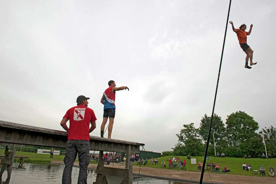 A canal vaulting contest gathers spectators in Linschoten, Netherlands. Another sport gaining popularity is the game of kolf, which involves hitting balls at two posts at the end of courts 60 feet long and 16 feet wide. Photo: HERMAN WOUTERS / NYTNS