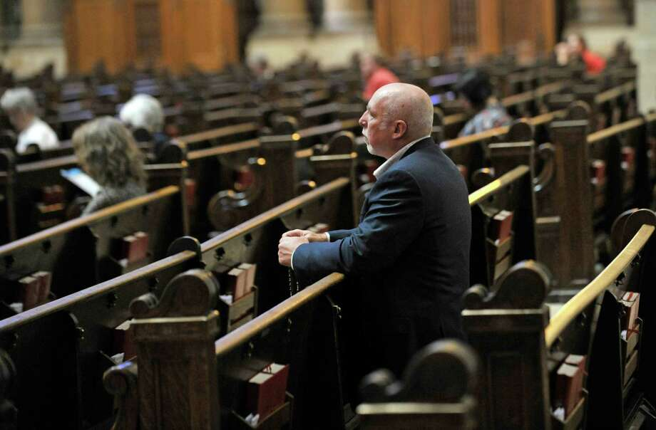 Frank Schubert, who has a lesbian sister, prays before Mass at St. Paul Cathedral in Minnesota. Schubert's focus is on the battle to keep gay marriage illegal. Photo: Jim Mone / AP