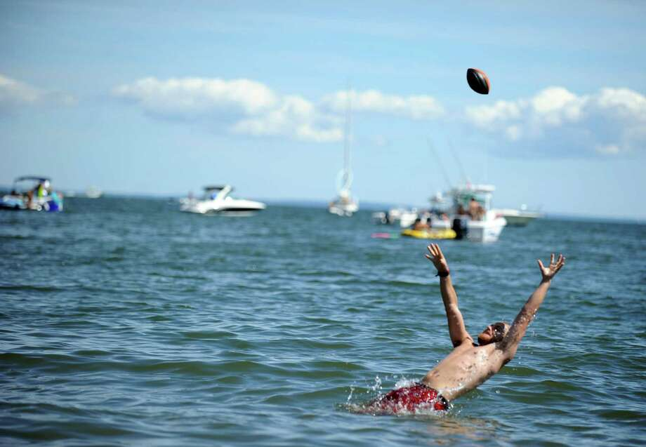 Daniel Murphy, of Brooklyn, NY, tries to catch a football while cooling off in the Long Island Sound during the Gathering of the Vibes at Seaside Park in Bridgeport, Conn. Saturday, July 21, 2012. Photo: Autumn Driscoll / Connecticut Post freelance
