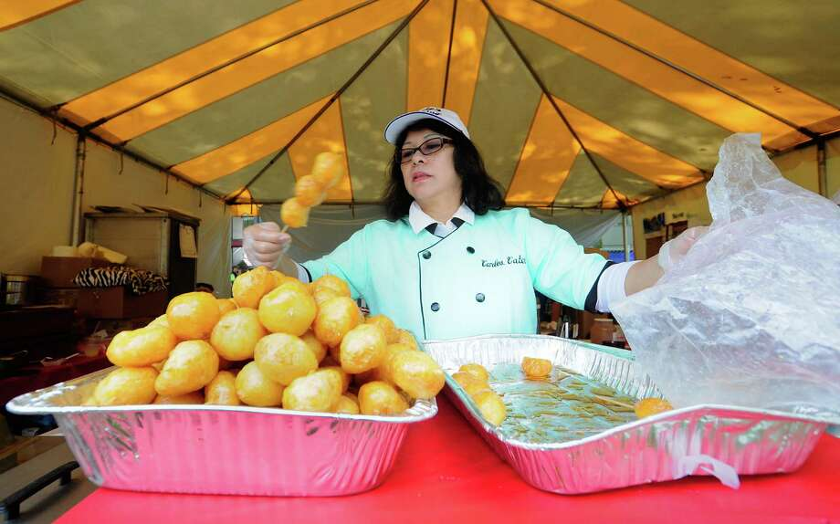 Anniebelle Segle prepares deep-fried sweet rice balls at the Carlos Catering booth during the Comcast Bite of Seattle at Seattle Center in Seattle on Friday, July 20, 2012. The event, which features more than 80 restaurant and food product booths, continues Saturday from 11 a.m. to 9 p.m. and Sunday from 11 a.m. to 8 p.m. Photo: LINDSEY WASSON / SEATTLEPI.COM