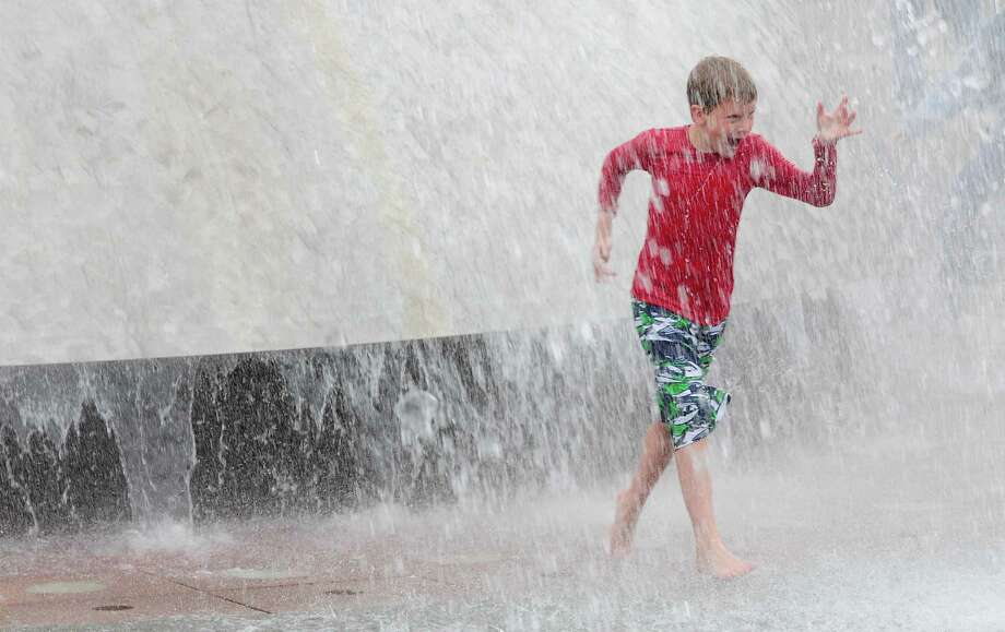 Timothy Walsh, 9, runs as he plays in the International Fountain. Photo: LINDSEY WASSON / SEATTLEPI.COM
