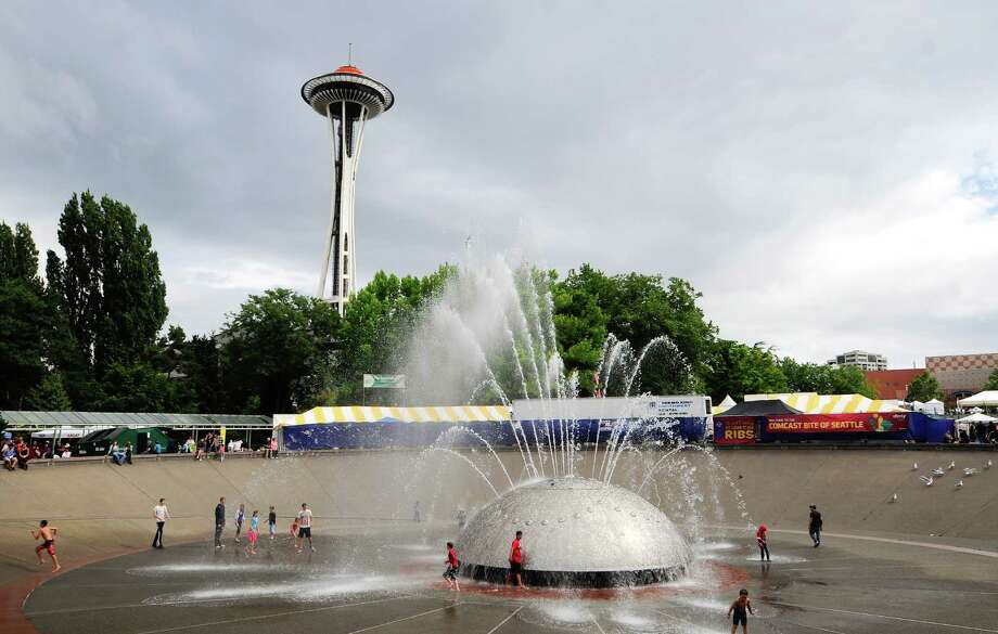A few people play in the International Fountain. Photo: LINDSEY WASSON / SEATTLEPI.COM