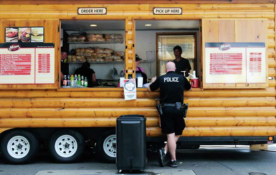 A police officer grabs some food from Trophy Spice. Photo: LINDSEY WASSON / SEATTLEPI.COM