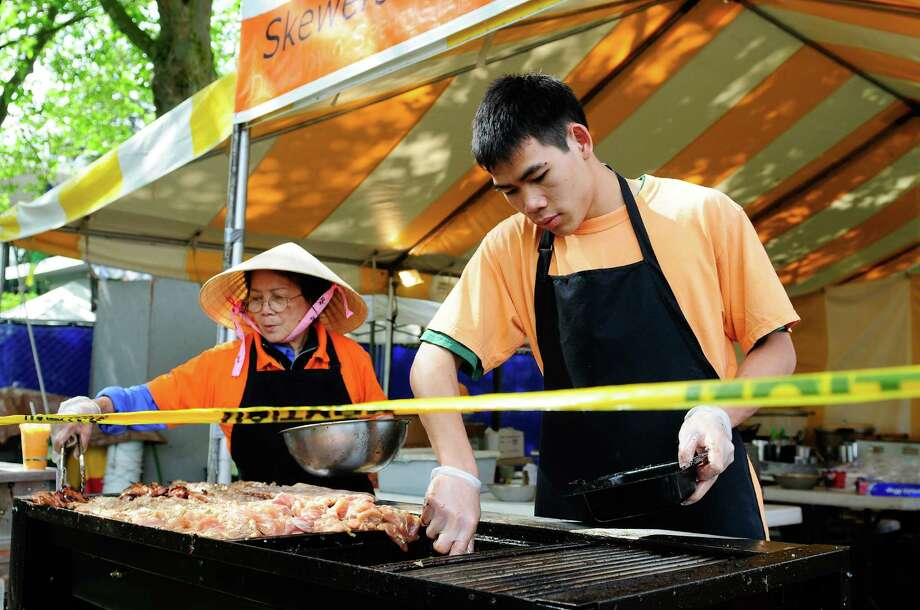 Chin Le and Quinhon Pham tend to meat on a grill at the Bambuza Vietnamese Bistro stand. Photo: LINDSEY WASSON / SEATTLEPI.COM