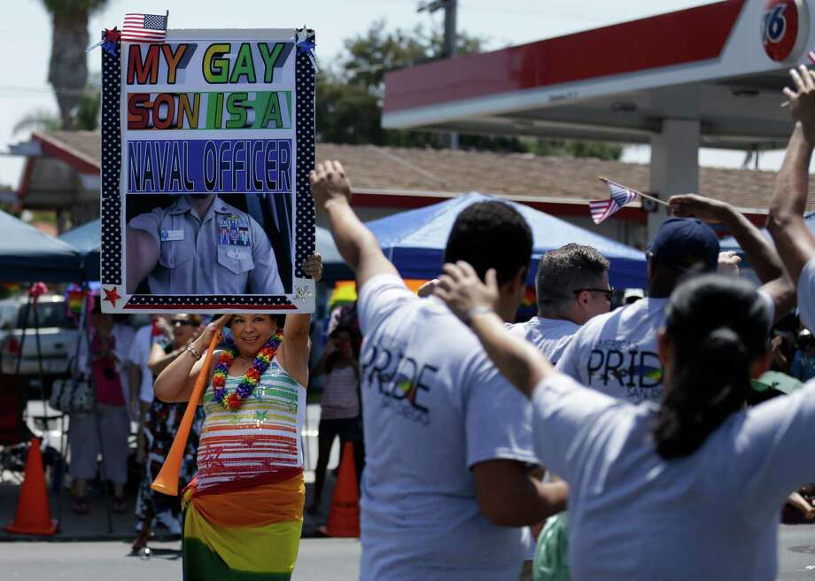 Betty Ayala salutes a group of veterans as she holds a sign showing her son during the gay pride parade Saturday, July 21, 2012, in San Diego. For the first time ever, U.S. service members marched in a gaypride event decked out in uniform Saturday, after a recent memorandum from the Defense Department to all military branches made an allowance for the San Diego parade - even though its policy generally bars troops from marching in uniform in parades. (AP Photo/Gregory Bull) Photo: Gregory Bull / AP