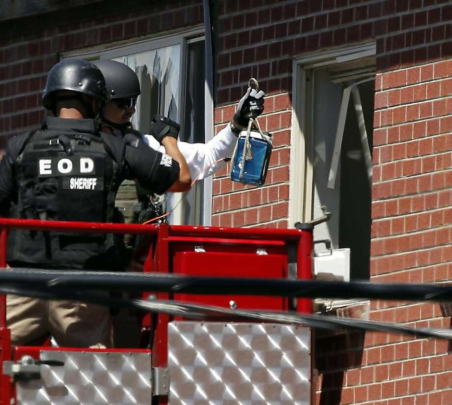 """Members of law enforcement wearing body armor and helmets prepare to what ATF sources describe as a""""water shot"""" in the apartment of alleged gunman James Holmes Saturday, July 21, 2012 in Aurora , Colo. The """"water shot"""" is exploded and used to disrupt the device. Authorities reported that 12 died and more than three dozen people were shot during an assault at a movie theatre midnight premiere of """"The Dark Knight Rises."""" (AP Photo/Alex Brandon) Photo: Alex Brandon, Associated Press"""