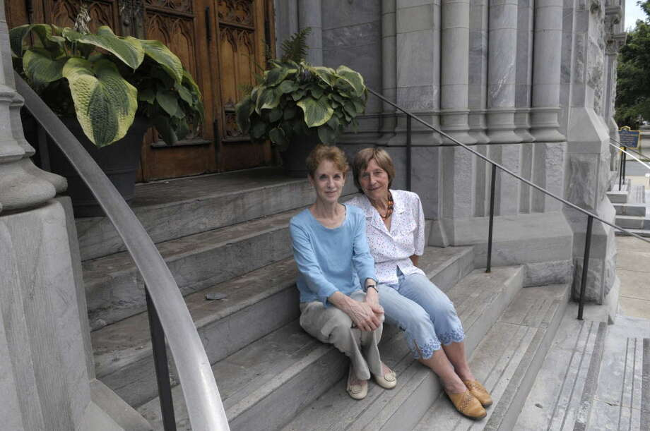 Lynn Kopka, left, president of Washington Park Association, and Hannelore Wilfert, a member of the Washington Park capital committee, sit on the front steps of St. Mary's Church on the corner of Third and Washington on Monday, July 18, 2011 in Troy. (Paul Buckowski / Times Union)