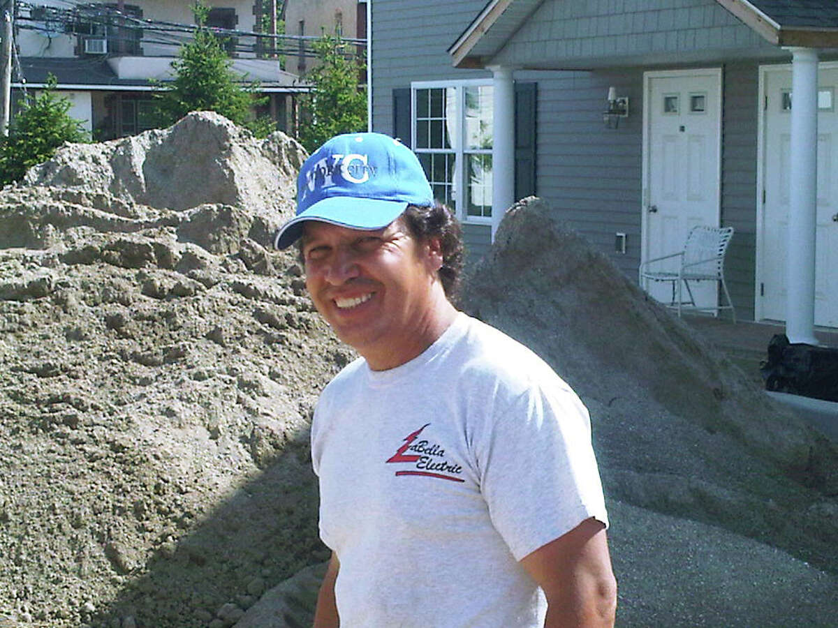 In this June 29, 2012 photo, site foreman Nicholas Gonzalez passes a large pile of sand in front of a unit at the Cottage Landings affordable housing project under construction in Rye, N.Y. The development is part of a 750-unit requirement in the settlement of a 2009 lawsuit against Westchester County. The county is being criticized by the federal government over its implementation of the settlement. (AP Photo/Jim Fitzgerald)
