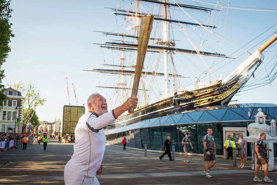 Sir Robin Knox Johnson, 73, the first person to sail solo around the world non-stop, carries the Olympic torch past the Cutty Sark ship on Saturday, July 21, 2012, in the Greenwich district of London. Day 64 of the Olympic Torch Relay took the flame for its first day through the streets of London, starting in the morning at the prime meridian in Greenwich, in a countdown to opening ceremonies of the London 2012 Olympic Games on July 27. Photo: Smiley N. Pool, Houston Chronicle / © 2012  Houston Chronicle