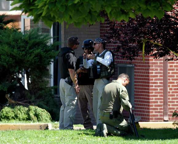 "Federal agents outside the apartment of James Holmes in Aurora, Colo., Saturday, July 21, 2012.  Federal authorities detonated one small explosive and disarmed another inside Holmes' apartment, but several other explosive devices remained, said Aurora police Sgt. Cassidee Carlson. Twelve people were killed and dozens were injured in a shooting attack early Friday at a packed movie theater during a showing of the Batman movie, ""The Dark Knight Rises.""   Police have identified Holmes, 24, as the suspected shooter. (AP Photo/Ed Andrieski) Photo: Ed Andrieski"