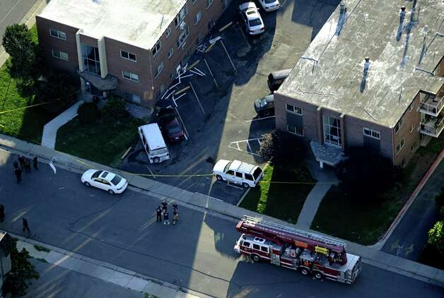 "Emergency crews, including a bomb squad unit, surround the apartment of alleged gunman James Holmes Saturday, July 21, 2012 in Aurora , Colo. The ""water shot"" is exploded and used to disrupt the device. Authorities reported that 12 died and more than three dozen people were shot during an assault at a movie theatre midnight premiere of ""The Dark Knight Rises."" (AP Photo/The Denver Post, Andy Cross) TV, INTERNET AND MAGAZINES CALL FOR RATES AND TERMS Photo: ANDY CROSS"