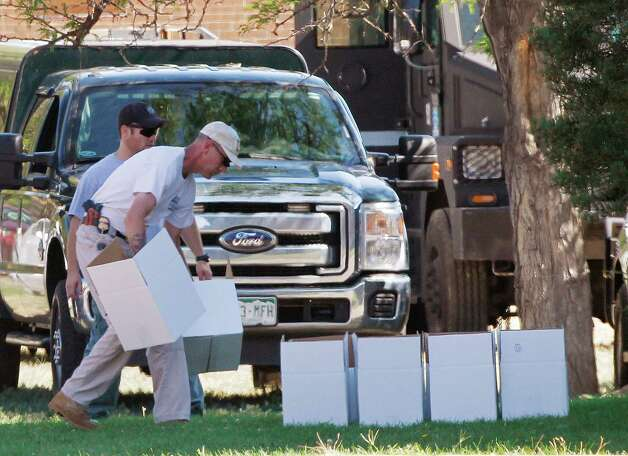 "An ATF agent arranges boxes for evidence in front of the apartment of James Holmes in Aurora, Colo., Saturday, July 21, 2012.  Federal authorities detonated one small explosive and disarmed another inside Holmes' apartment, but several other explosive devices remained, said Aurora police Sgt. Cassidee Carlson. Twelve people were killed and dozens were injured in a shooting attack early Friday at a packed movie theater during a showing of the Batman movie, ""The Dark Knight Rises.""   Police have identified Holmes, 24, as the suspected shooter. (AP Photo/Ed Andrieski) Photo: Ed Andrieski"