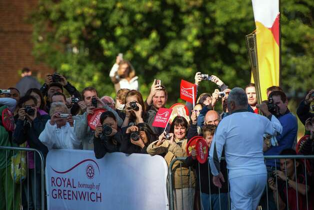 Sir Robin Knox Johnson, 73, the first person to sail solo around the world non-stop, carries the Olympic torch past a crowd of spectators on Saturday, July 21, 2012, in the Greenwich district of London. Photo: Smiley N. Pool, Houston Chronicle / © 2012  Houston Chronicle