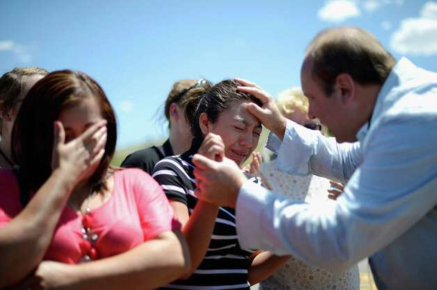 AURORA, CO - JULY 21:  Haley Zuyapa, 13, and her mother react as they pray for victims of the Century 16 movie theatre where a gunmen attacked movie goers during an early morning screening of the new Batman movie 'The Dark Knight Rises' on July 21, 2012 in Aurora, outside of Denver, Colorado. According to reports, 12 people were killed and 59 wounded when James Holmes allegedly opened fire inside the theater. Police have Holmes 24, of North Aurora, in custody  (Photo by Kevork Djansezian/Getty Images) Photo: Kevork Djansezian