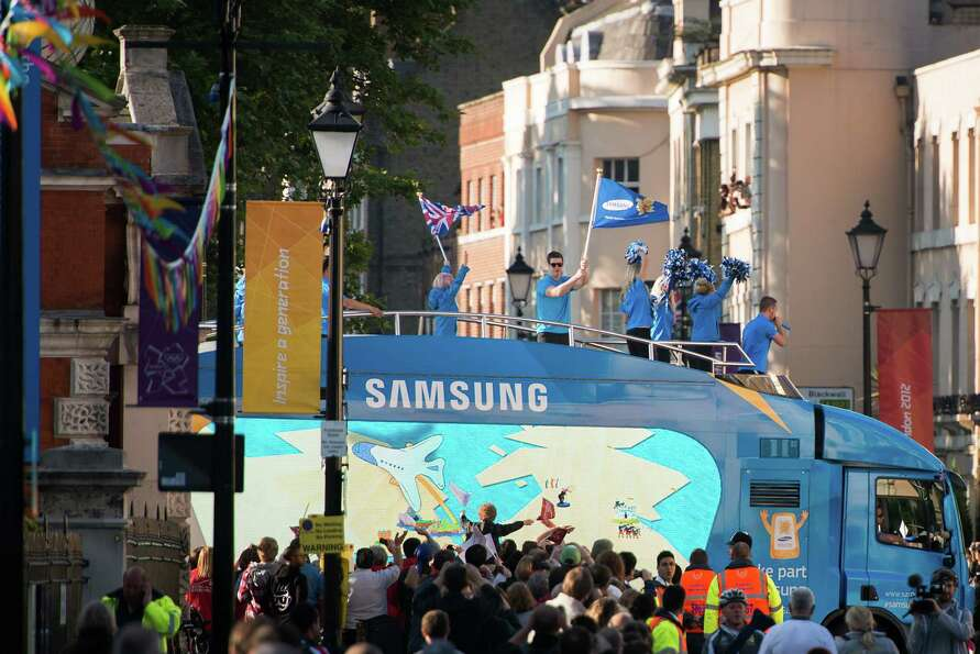 People wave from atop a sponsor vehicle as crowds lining the street wait to view the Olympic torch r