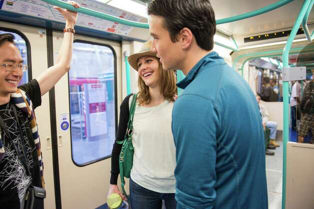 "Houstonians Lydia and Eric McGuire, right, chat with Ken Tan, left, as they ride the Docklands Light Railway after watching the Olympic torch relay on Saturday, July 21, 2012, in London. The couple has been living in London for six weeks. ""We moved here just in time for the Olympics,"" Lydia McGuire said. Photo: Smiley N. Pool, Houston Chronicle / © 2012  Houston Chronicle"
