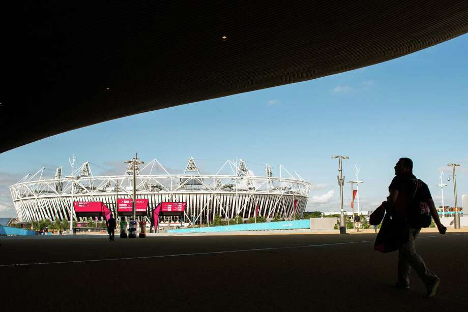 Workers pass through the shade from the Aquatics Centre as they walk toward the Olympic Stadium in the Olympic Park as preparations continue for the London 2012 Olympics on Saturday, July 21, 2012, in London. Photo: Smiley N. Pool, Houston Chronicle / © 2012  Houston Chronicle