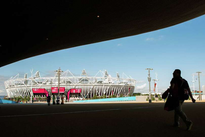 Workers pass through the shade from the Aquatics Centre as they walk toward the Olympic Stadium in t
