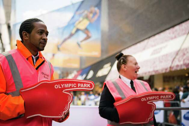 Security personnel direct visitors passing though the Westfield Stratford City Shopping Centre toward the Olympic Park as preparations for the 2012 Summer Olympics continue on Saturday, July 21, 2012, in London. Photo: Smiley N. Pool, Houston Chronicle / © 2012  Houston Chronicle