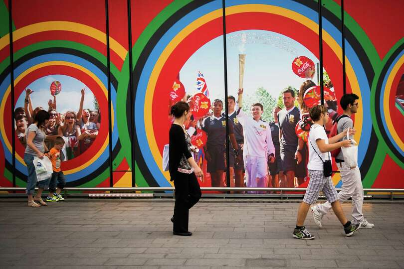 Pedestrians pass murals near the Olympic Park showing images from the Olympic torch run as preparati