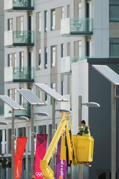 Workers install banners on light poles near the athletes village in preparation for the 2012 Summer