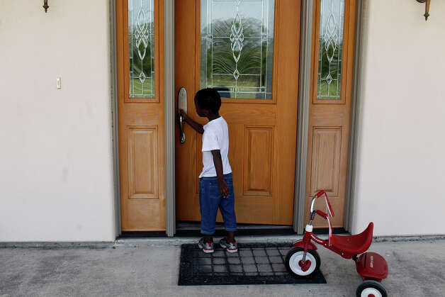 John Kulimushi, 4, goes inside his new home after riding a tricycle on Saturday, July 21, 2012, at the home of Scott and Nancy Hagerup, where he and his family are living since being evicted from their San Antonio apartment Tuesday. Photo: Lisa Krantz, San Antonio Express-News / San Antonio Express-News