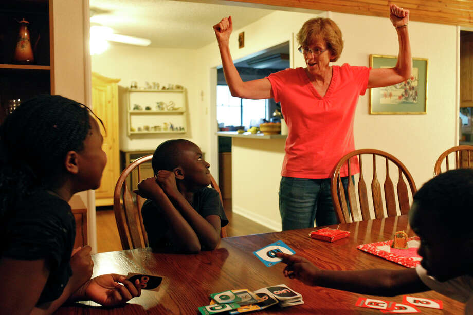 "Nancy Hagerup celebrates as Elisha Kulimushi, 8, center, wins a game of Uno at her home in Seguin on Saturday, July 21, 2012.  Kulimushi, with his seven siblings including Ortance Kulimushi, 10, left, and Shokano ""Luke"" Kulimushi, 6, right, and their mother are living with the Hagerups since being evicted from their San Antonio apartment Tuesday. Photo: Lisa Krantz, San Antonio Express-News / San Antonio Express-News"