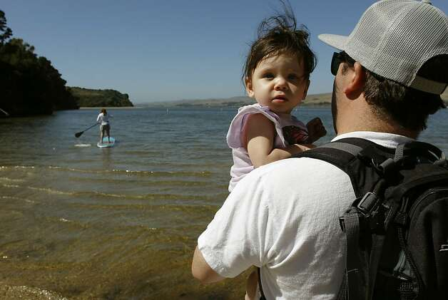 Rob Skehan and daughter Natalie, 7 months watch from shore as mom, Melissa paddle boards out into the waters at Tomales Bay State Park, in Marin County, Ca., on Saturday July 21 2012. California State Parks have found $54 million which means that the $22 million deficit they said was the reason why they had to close parks was completely false. Photo: Michael Macor, The Chronicle