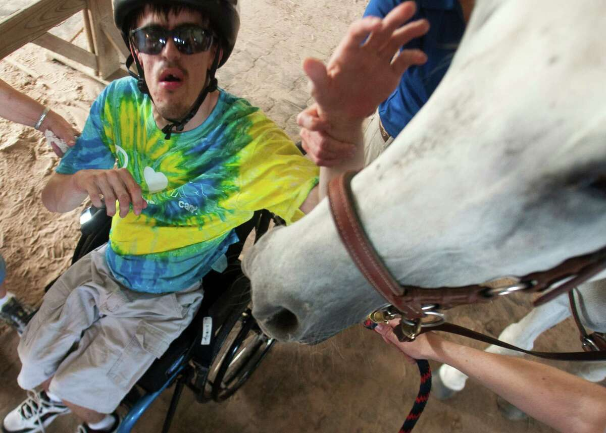 Derek Blackburn, 25, pets Tikki, a therapeutic horse, at the SIRE facility. Equine therapy is a rapidly expanding tool to help people with disabilities.