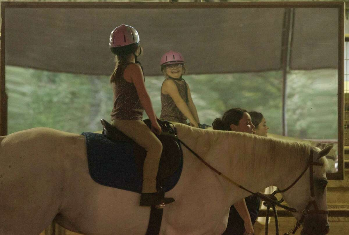 Kalyn Adkins, 10, smiles at herself as she rides at the SIRE facility in Hockley last week. Kalyn, who has Down syndrome, has become more assertive and talkative since she began riding, her mother says.