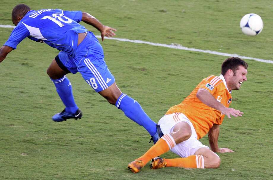 Dynamo forward Will Bruin heads the ball past Montreal Impact midfielder Collen Warner during the first half. Photo: J. Patric Schneider, For The Chronicle / Houston Chronicle