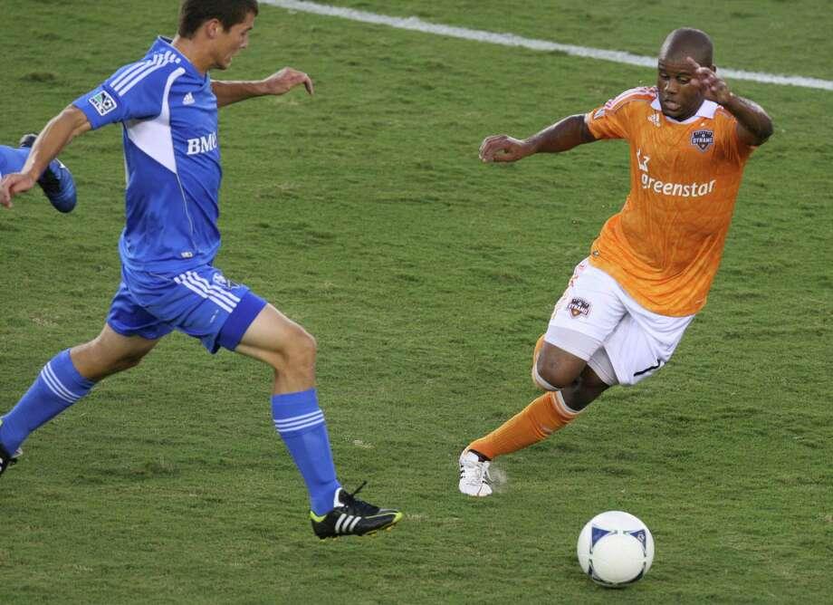 Dynamo midfielder Luiz Camargo dribbles past Impact defender Karl Ouimette. Photo: J. Patric Schneider, For The Chronicle / Houston Chronicle