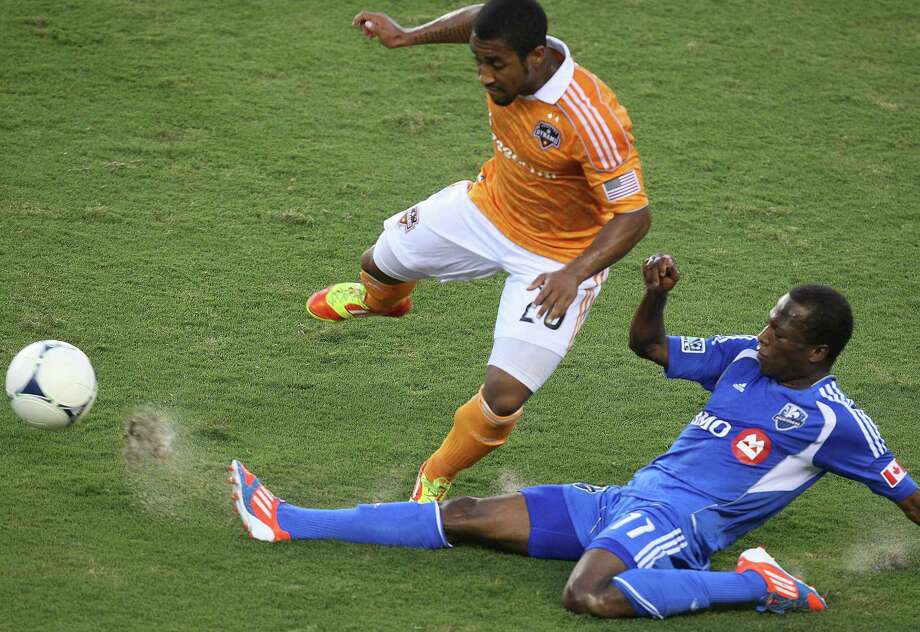 Impact midfielder Sanna Nyassi tackles defender Corey Ashe. Photo: J. Patric Schneider, For The Chronicle / Houston Chronicle