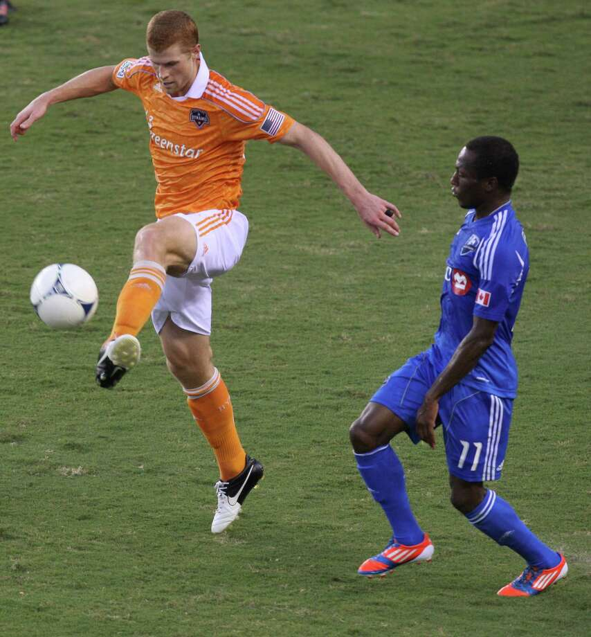 Dynamo defender Andre Hainault kicks the ball past midfielder Sanna Nyassi during the first half. Photo: J. Patric Schneider, For The Chronicle / Houston Chronicle
